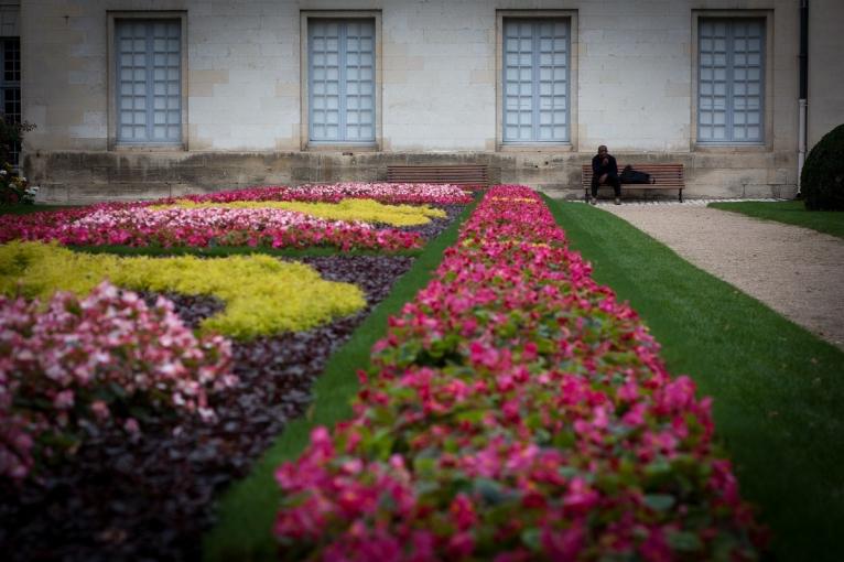 Dans le jardin du musée des beaux-arts, un homme attend, sur un banc. La masse colorée des parterres répond à la rigueur, limite austère, du mur et des fenêtres.