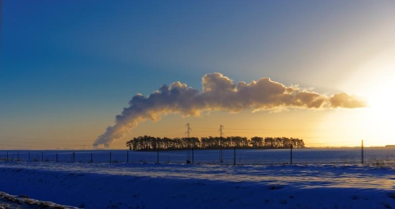 La centrale nucléaire de Blois enrobe un bois d'un panache de vapeur. C'est le petit matin, la neige recouvre la campagne.